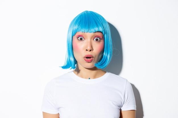 Imagem de uma linda garota asiática com fantasia de halloween e peruca azul, parecendo surpresa, em pé.