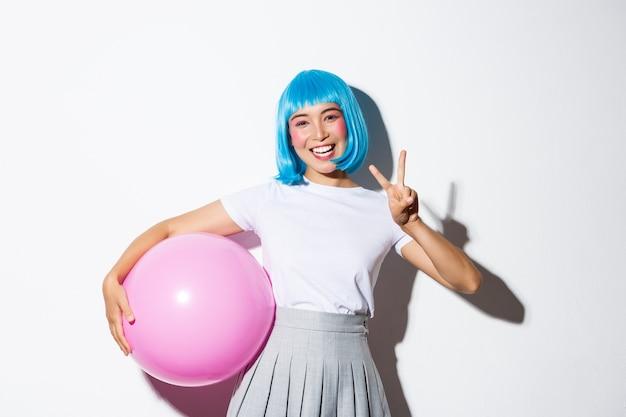 Imagem de uma linda garota asiática com peruca azul e fantasia de halloween, mostrando um gesto de paz, segurando um grande balão rosa.