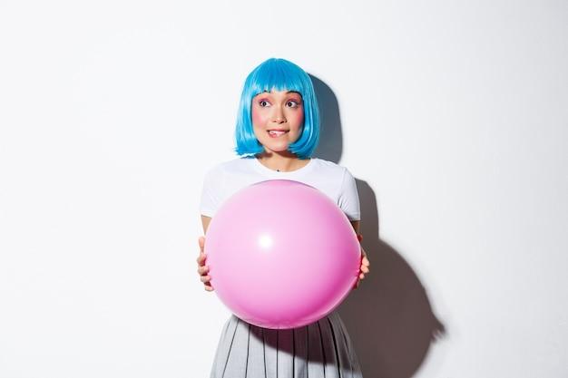 Imagem de uma linda garota asiática indecisa olhando para a esquerda, segurando um grande balão rosa, vestida de personagem de anime para a festa de halloween.