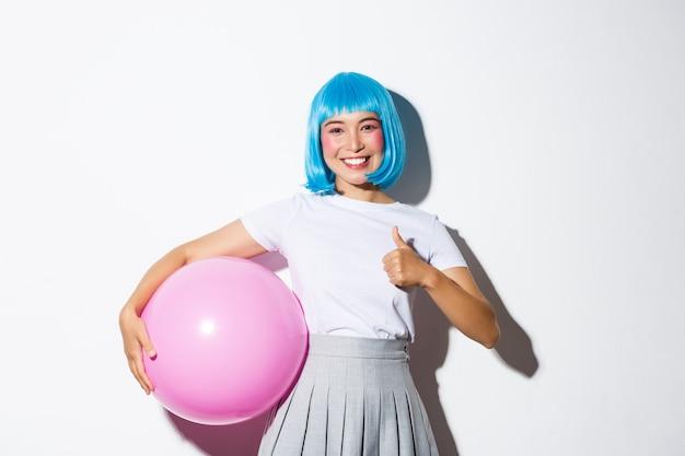Imagem de uma linda garota asiática na peruca azul e fantasia de halloween, mostrando o polegar para cima, segurando um grande balão rosa.