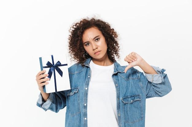 Imagem de uma linda jovem africana descontente posando isolada sobre uma parede branca, segurando a caixa de presente presente mostrando os polegares para baixo.