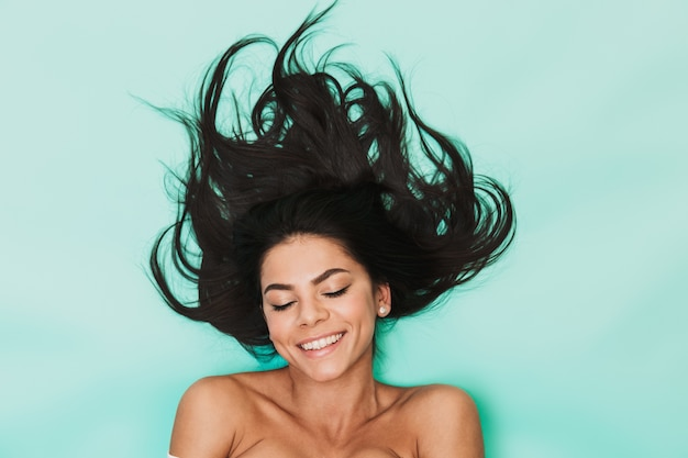 Imagem de uma linda jovem feliz satisfeita encontra-se isolada na luz azul. conceito de cabelo saudável.