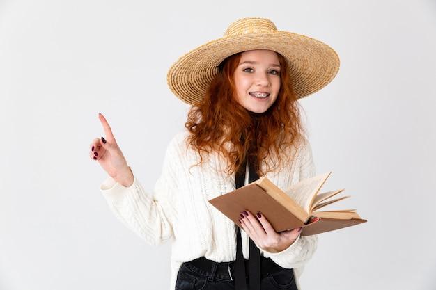 Imagem de uma linda jovem ruiva linda garota posando isolado sobre o fundo da parede branca, segurando a leitura do livro.