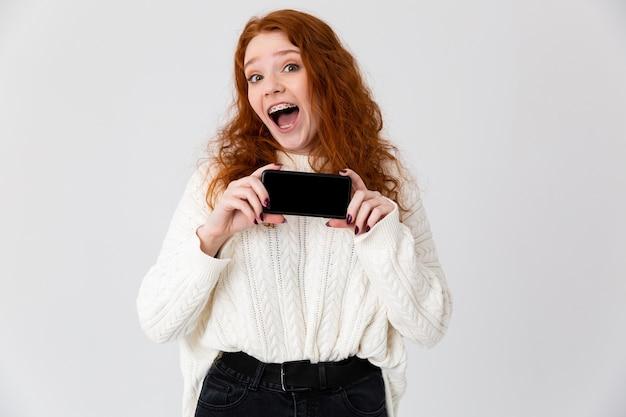 Imagem de uma linda jovem ruiva posando isolado sobre o fundo da parede branca, mostrando o visor do telefone móvel.