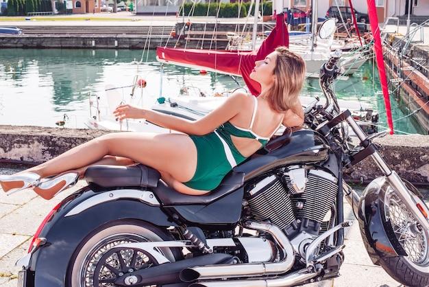 Imagem de uma linda loira elegante em um biquíni verde deitada em uma enorme motocicleta. o conceito de automobilismo, turismo, estilo de moda. mídia mista