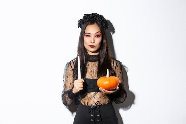 Imagem de uma linda mulher asiática na fantasia de bruxa, segurando uma vela acesa e abóbora, comemorando o dia das bruxas.