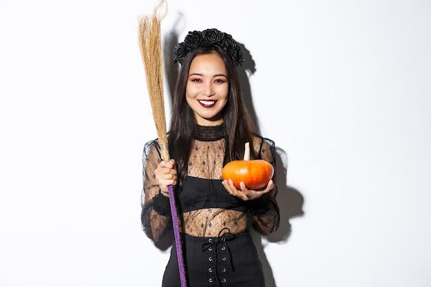 Imagem de uma linda mulher asiática vestida de bruxa para a festa de halloween, segurando uma vassoura e uma abóbora, em pé sobre uma parede branca