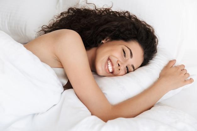 Imagem de uma linda mulher de 20 anos com cabelo escuro e encaracolado sorrindo, deitada na cama em um travesseiro branco após dormir