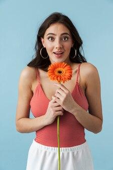Imagem de uma linda mulher jovem e animada bonita posando isolada sobre uma parede azul, segurando uma flor.