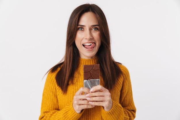 Imagem de uma linda mulher morena adulta sorrindo e segurando uma barra de chocolate isolada no branco