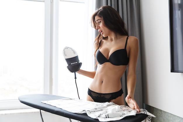 Imagem de uma linda mulher morena animado chocado vestindo lingerie em casa dentro de casa camisa de ferros.