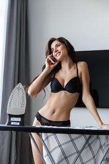 Imagem de uma linda mulher morena feliz vestindo lingerie em casa dentro de casa ferros camisa falando por telefone celular.