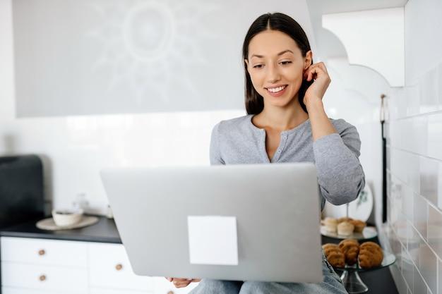 Imagem de uma linda mulher morena sentada na cozinha e usando o laptop
