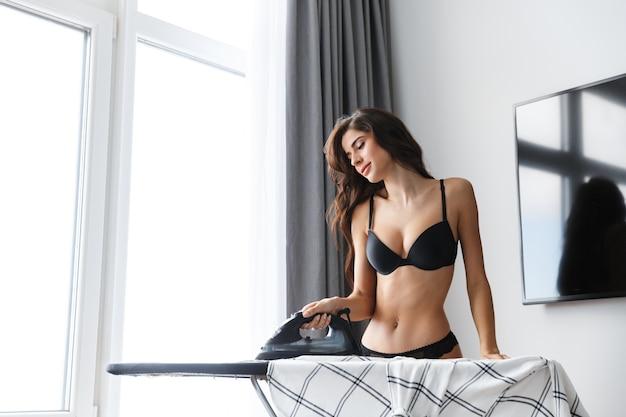 Imagem de uma linda mulher morena usando lingerie em casa dentro de casa camisa de ferros.