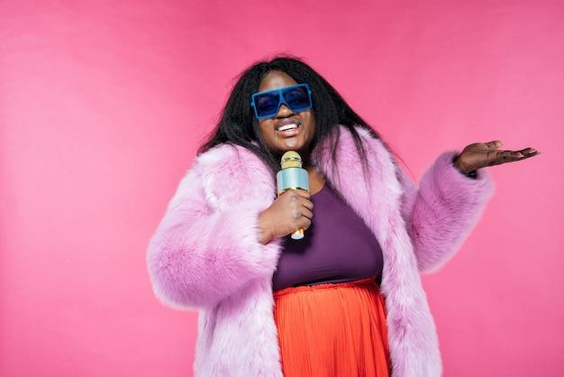 Imagem de uma linda mulher posando com um casaco de pele em um fundo rosa