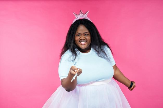 Imagem de uma linda mulher posando com uma fantasia de fada em um fundo rosa