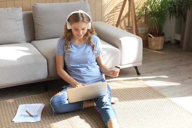 Imagem de uma linda mulher trabalhando com o laptop enquanto está sentado no chão em casa.
