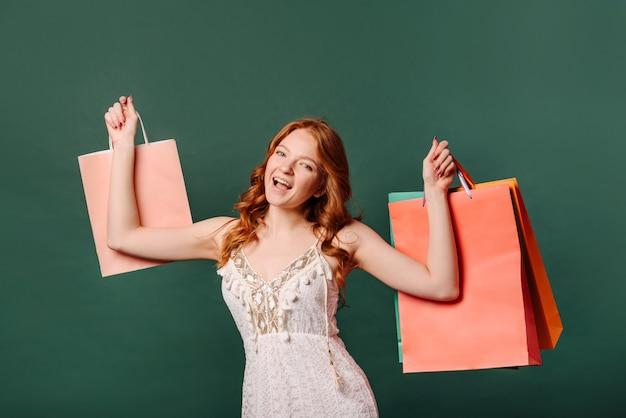 Imagem de uma linda ruiva jovem feliz posando contra uma parede verde com sacos nas mãos dela.