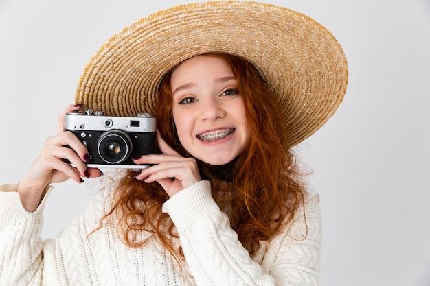 Imagem de uma linda ruiva linda jovem feliz posando isolado sobre o fundo da parede branca, usando o chapéu, segurando a câmera.