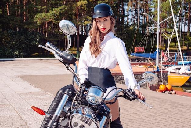 Imagem de uma loira deslumbrante e elegante em uma camisa branca e capacete preto, pilotando uma enorme motocicleta. o conceito de automobilismo, turismo, estilo de moda. mídia mista