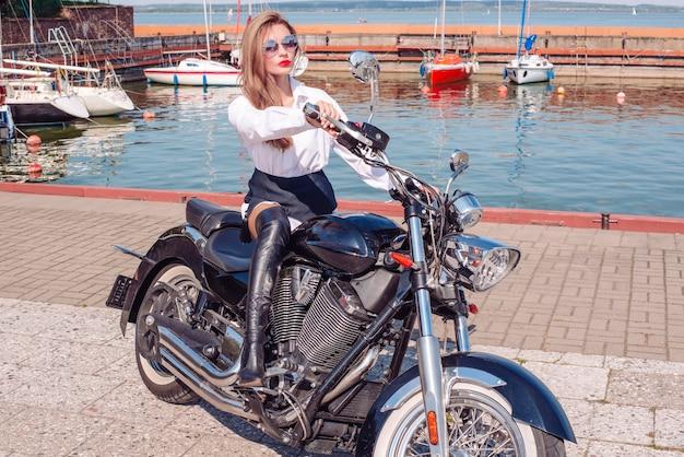 Imagem de uma loira deslumbrante e elegante em uma camisa branca, pilotando uma enorme motocicleta. o conceito de automobilismo, turismo, estilo de moda. mídia mista