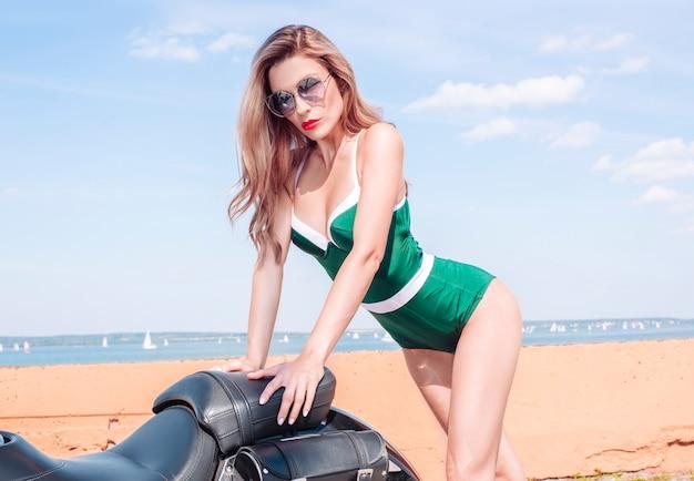 Imagem de uma loira deslumbrante e estilosa em um biquíni verde ao lado de uma enorme motocicleta. o conceito de automobilismo, turismo, estilo de moda. mídia mista