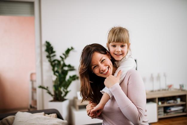 Imagem de uma mãe feliz que reboca a filha pequena adorável. olhando para a câmera