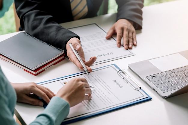 Imagem de uma mão de mulher segurando uma caneta, lendo um currículo com documentos do contrato no escritório.