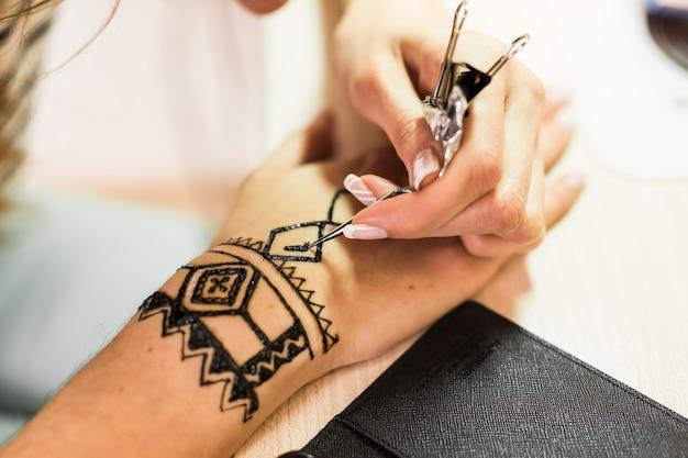 Imagem de uma mão humana sendo decorada com henna. mão mehendi.