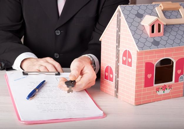 Imagem de uma mesa de escritório com uma casa de madeira e um consultor imobiliário entregando a chave