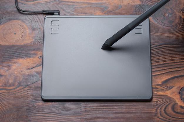Imagem de uma mesa digitalizadora, caneta e laptop em uma mesa de madeira. local de trabalho do designer.