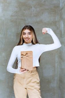 Imagem de uma modelo de garota segurando um presente de papel com um arco sobre uma pedra