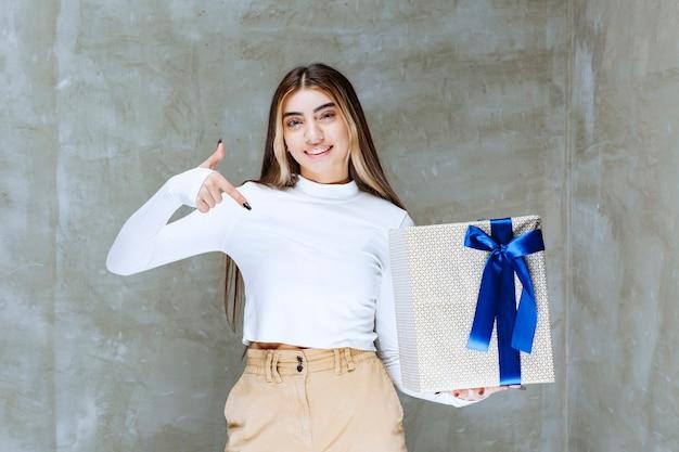 Imagem de uma modelo de menina apontando para uma caixa de presente com um arco isolado sobre uma pedra