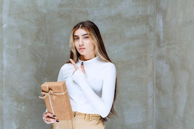Imagem de uma modelo de menina com um presente de papel apontando para longe sobre uma pedra