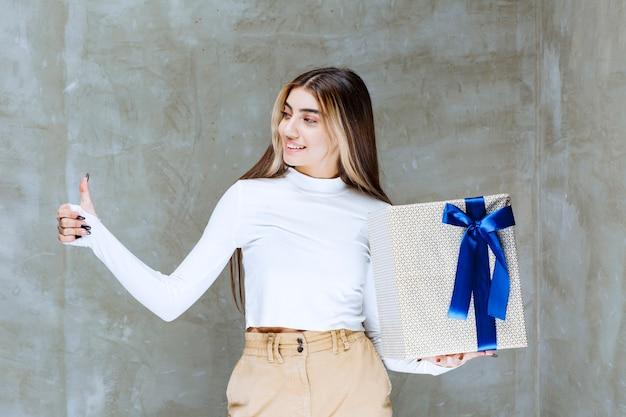Imagem de uma modelo de menina com uma caixa de presente mostrando o polegar sobre uma pedra