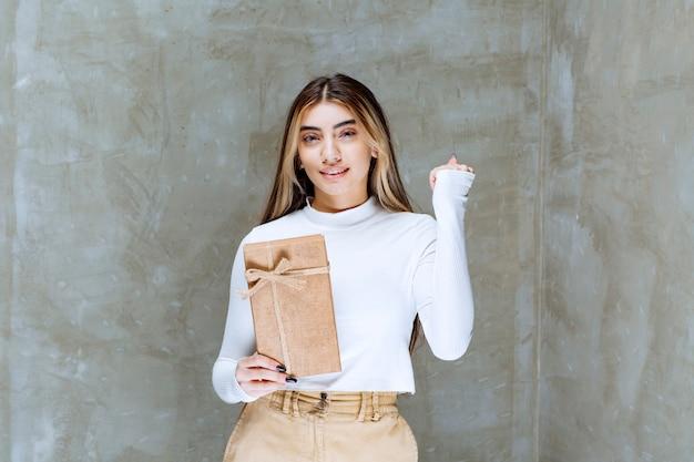 Imagem de uma modelo de menina segurando um presente de papel sobre uma pedra