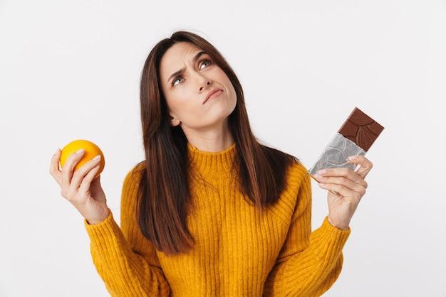 Imagem de uma mulher adulta morena duvidosa hesitando enquanto segura uma barra de laranja e chocolate isolada no branco