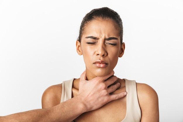 Imagem de uma mulher africana com medo, descontente, posando enquanto a mão de alguém segurando seu pescoço.
