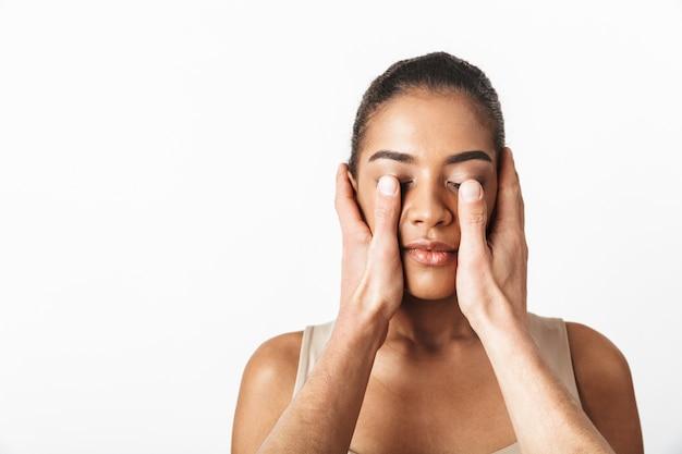 Imagem de uma mulher africana posando enquanto as mãos de alguém cobrindo os olhos.