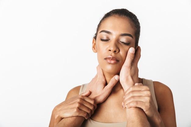 Imagem de uma mulher africana posando enquanto as mãos de alguém tocando seu pescoço.