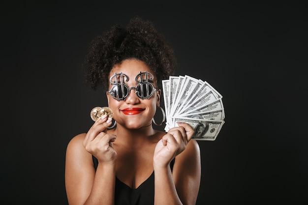 Imagem de uma mulher afro-americana chique usando óculos de dólar, segurando um bitcoin dourado e notas de dinheiro