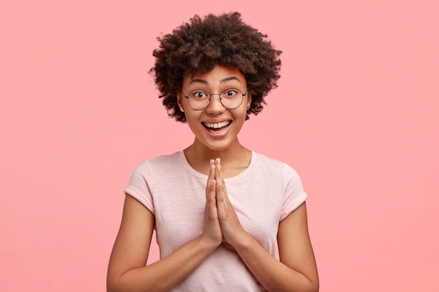 Imagem de uma mulher afro-americana feliz com um sorriso agradável, vestida casualmente, junta as mãos, posa em gesto de oração, implorando perdão com expressão alegre, isolada na parede rosa