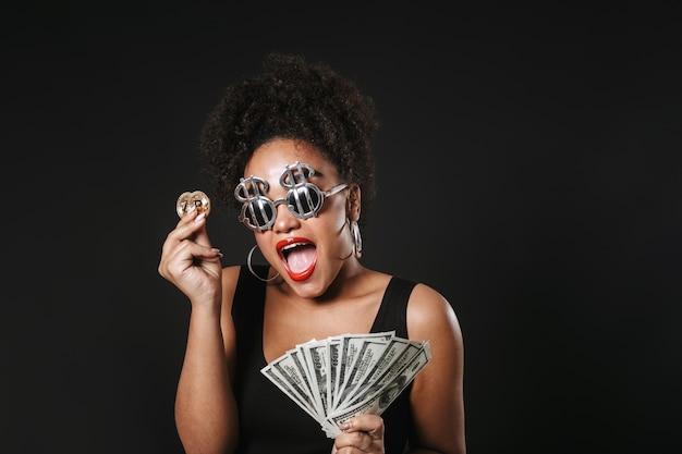 Imagem de uma mulher afro-americana feliz usando óculos de dólar segurando um bitcoin dourado e notas de dinheiro