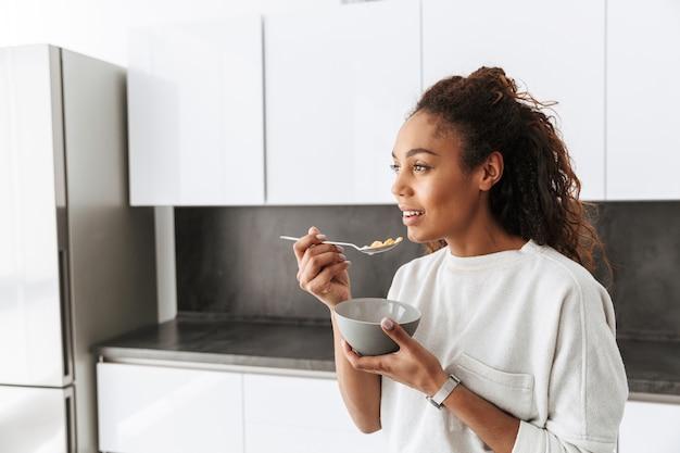 Imagem de uma mulher afro-americana saudável comendo flocos de milho com leite no café da manhã, em uma cozinha elegante