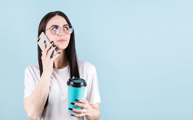 Imagem de uma mulher americana feliz sorrindo e ligando para um amigo enquanto bebia café