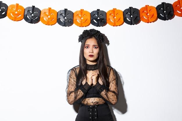 Imagem de uma mulher asiática assustada e preocupada com fantasia de bruxa, parecendo preocupada, vestindo fantasia de bruxa e em pé contra bandeiras de abóbora.
