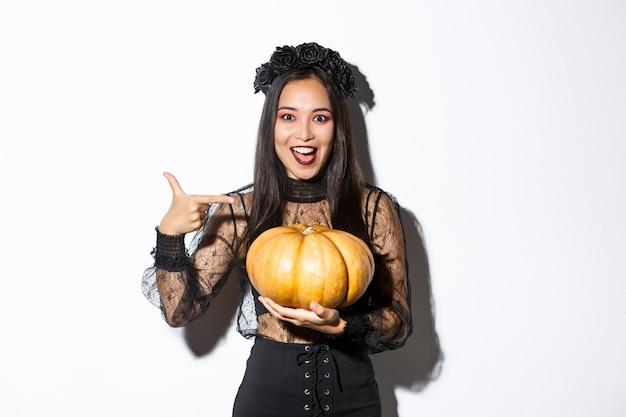 Imagem de uma mulher asiática empolgada com maquiagem gótica, usando um vestido preto de bruxa e segurando uma abóbora, parada na parede branca