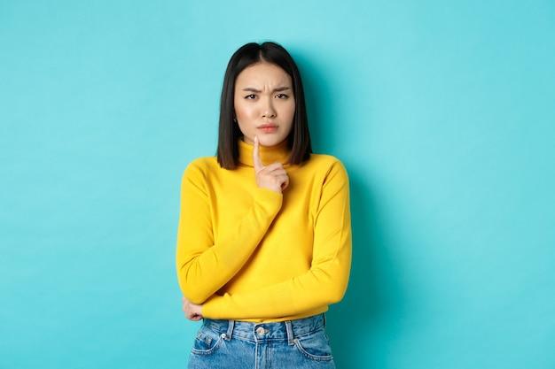 Imagem de uma mulher asiática pensativa tocando o lábio e franzindo a testa, pensando em algo, tentando entender, em pé sobre um fundo azul