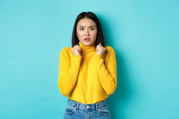 Imagem de uma mulher asiática preocupada com cabelo escuro curto, apertando as mãos e olhando para a câmera em questão, em pé sobre um fundo azul