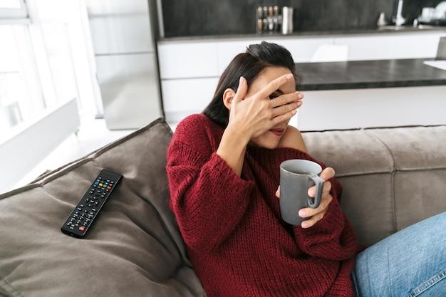 Imagem de uma mulher assustada emocional dentro de casa em casa no sofá assistir tv bebendo café cobrindo os olhos.